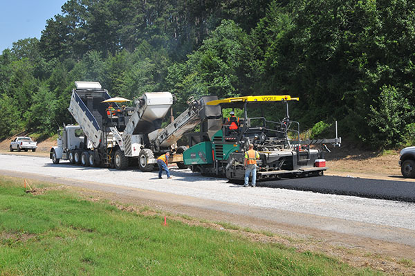 An asphalt paving train makes its way along the pulverized concrete base. Multiple layers of asphalt are required to build up the roadway and support years of constant traffic.